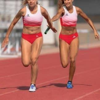 deux femmes qui courent sur une piste rouge d'athlétisme, habillés avec brassières et bloomers rouges